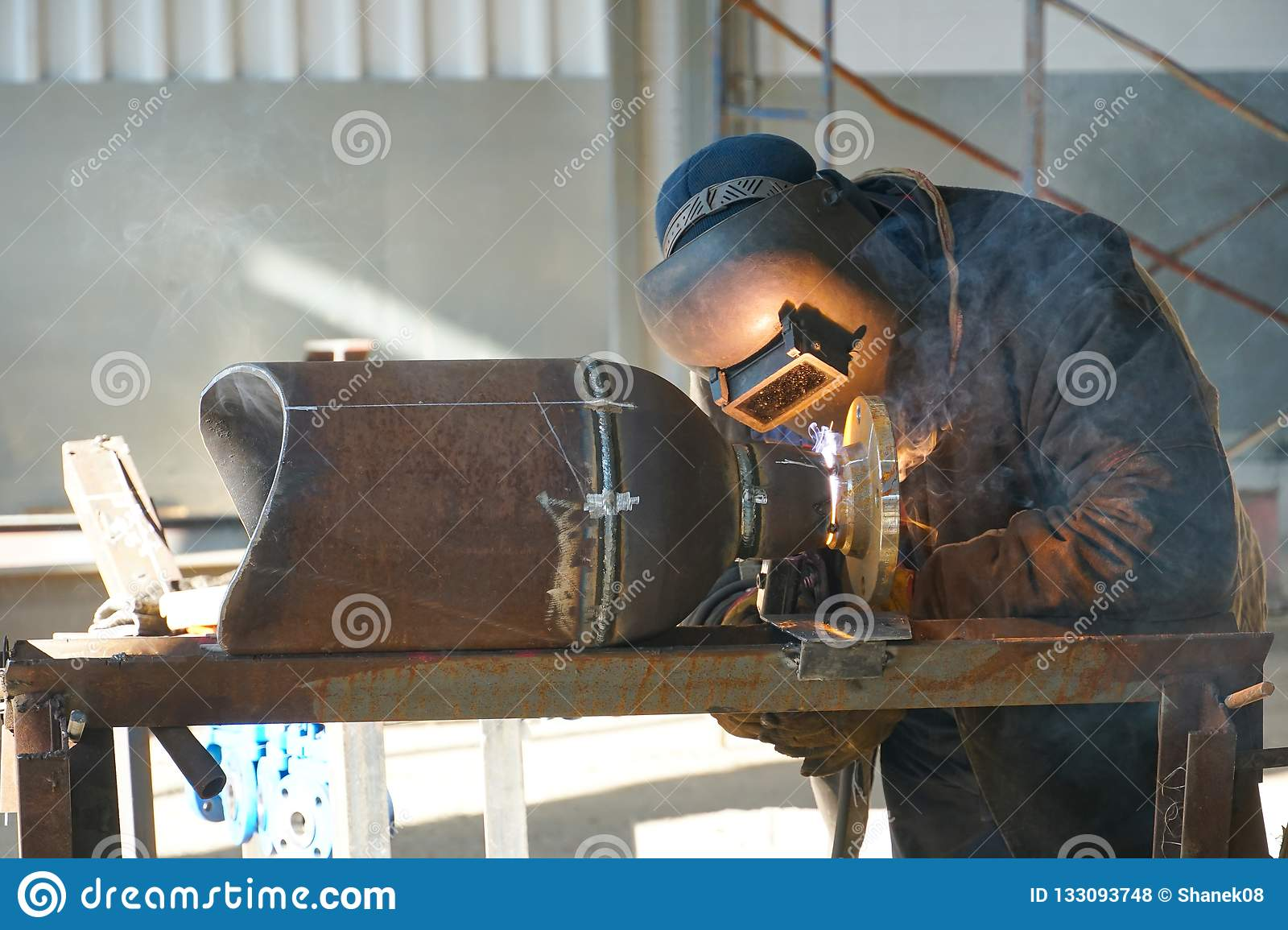 Manual electric arc welding of the junction Du 100 and flange