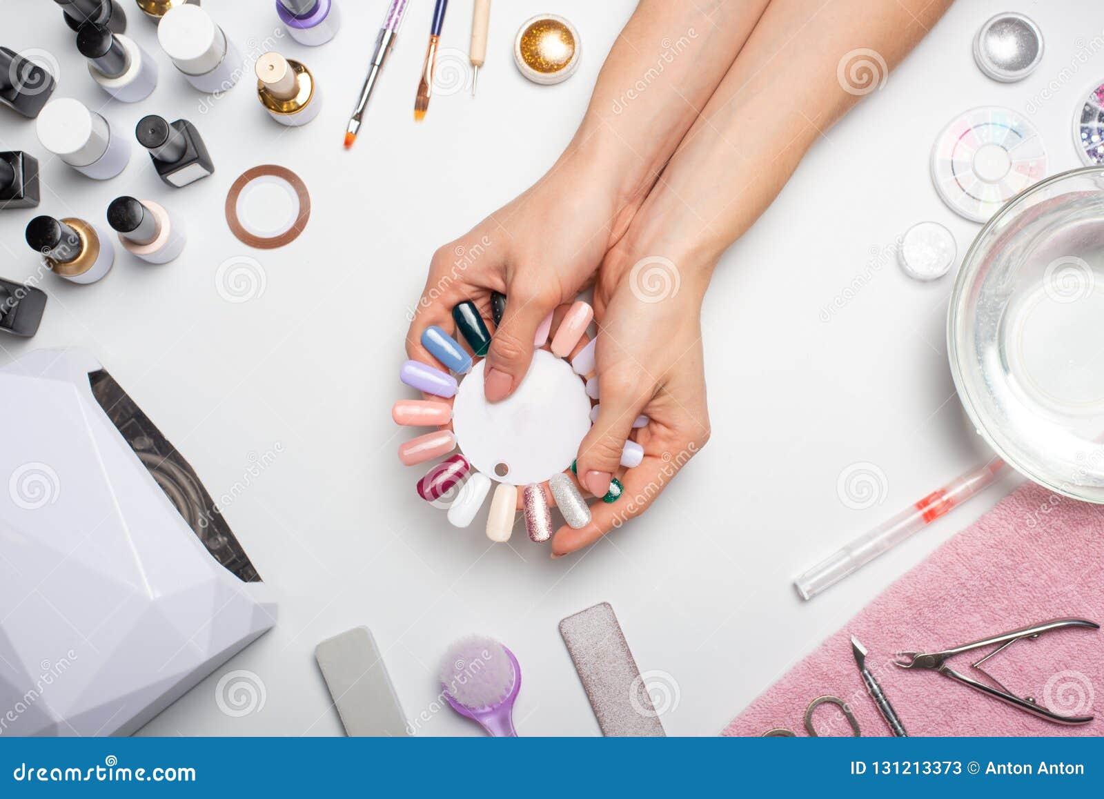 Manucure - la fille elle-même fait, observant les ongles à l aide d un outil sur un fond blanc Concept des salons de beauté et de