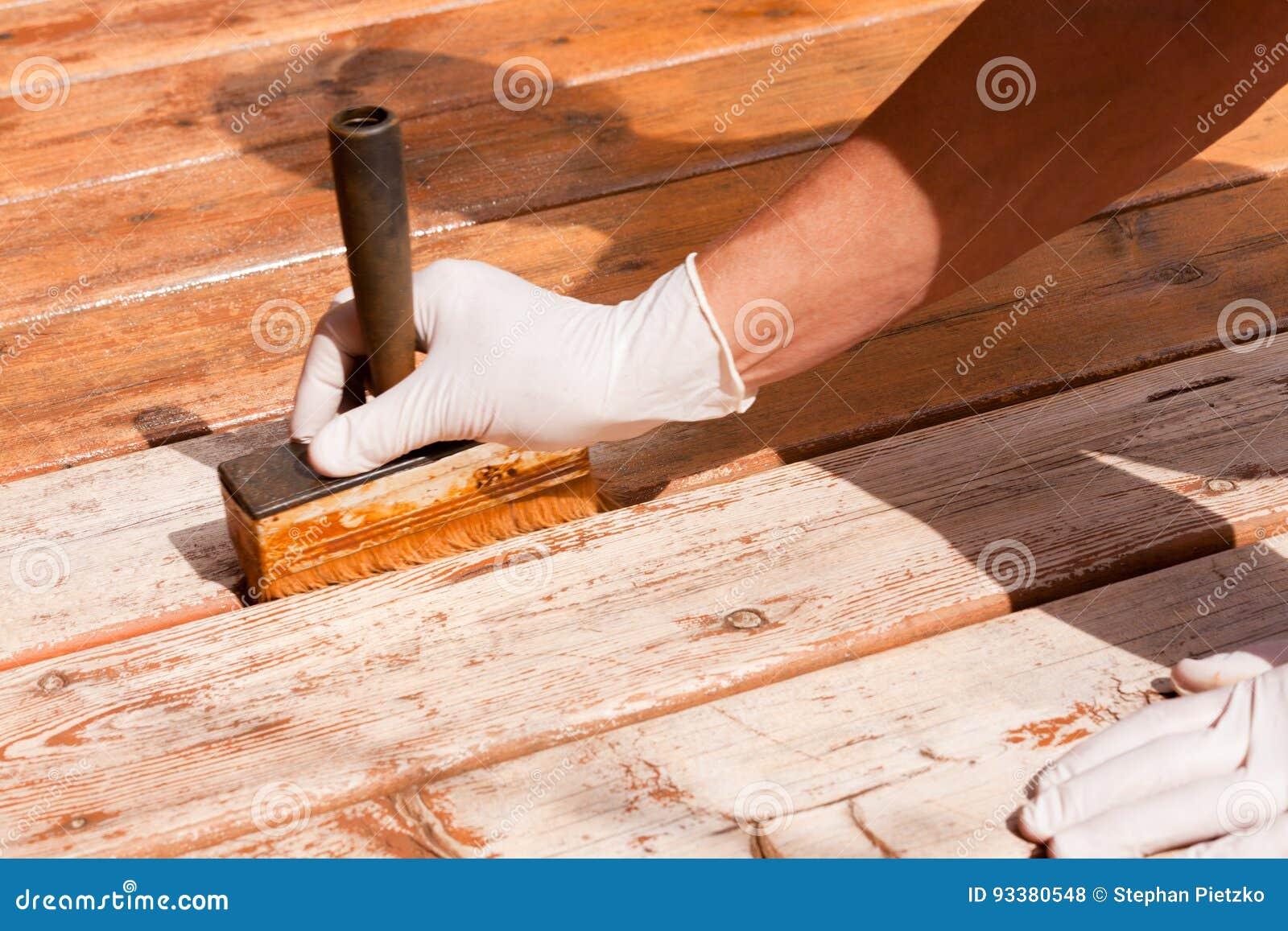 A manutenção da plataforma aplica a mancha no decking de madeira