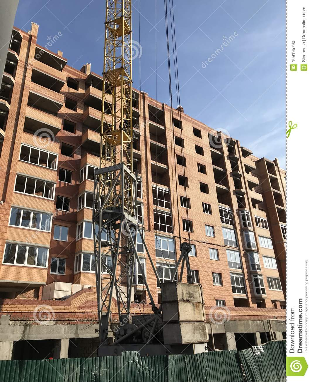 A Giant Crane In Front Of A New Apartment Being ...