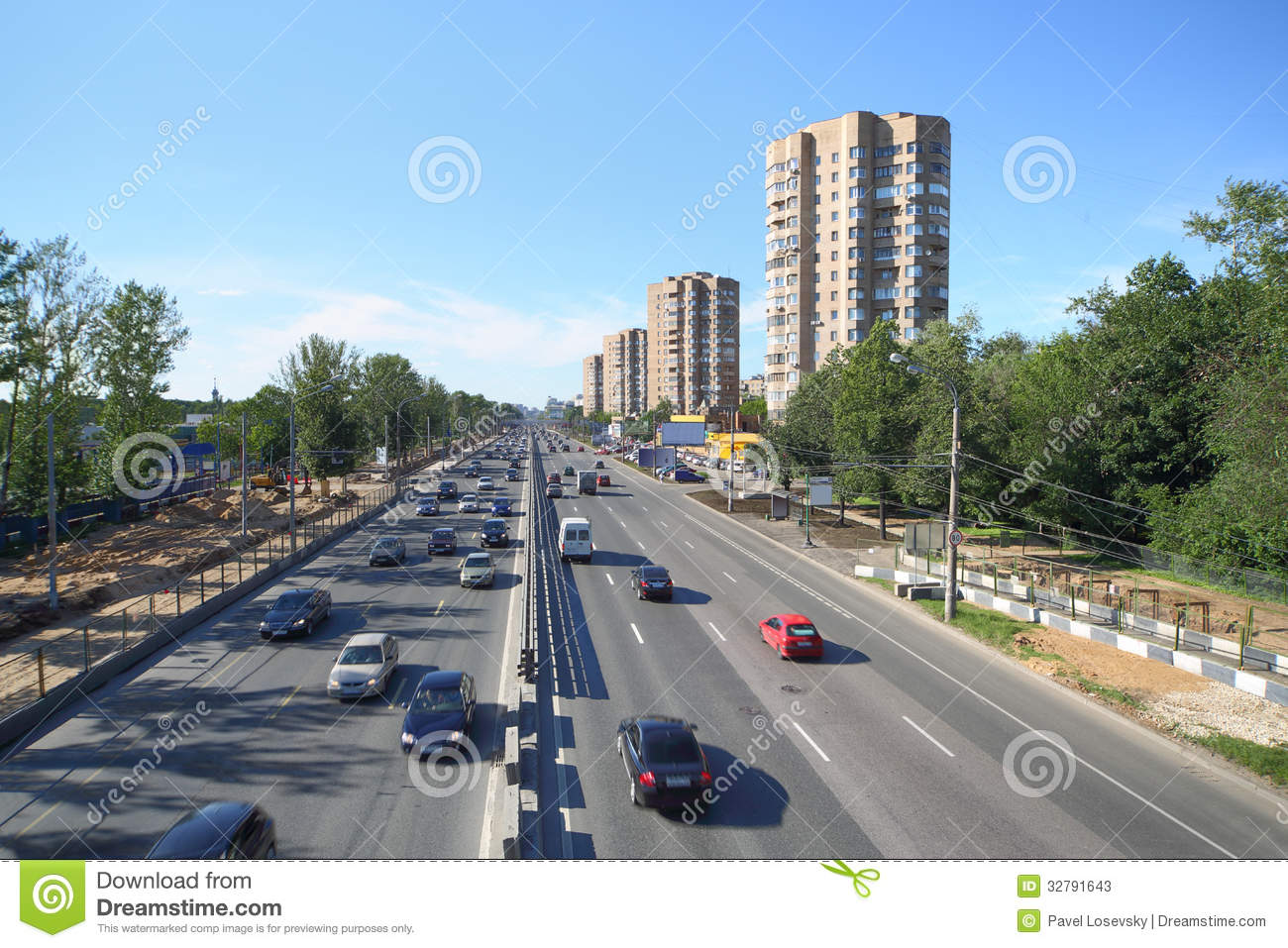 Many cars goes on wide road in large city
