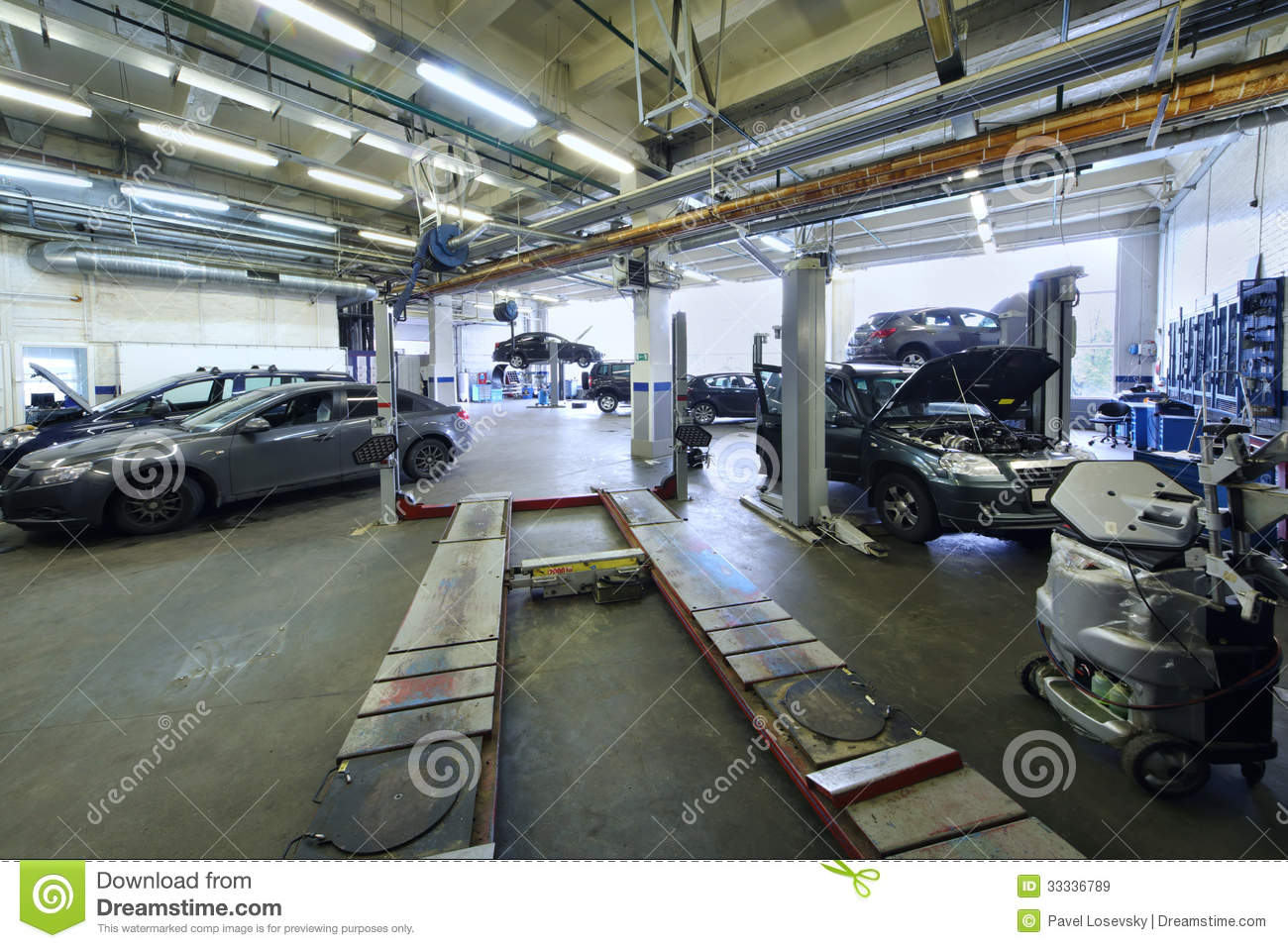 Many cars stand in car garage with special equipment for Equipement complet garage auto