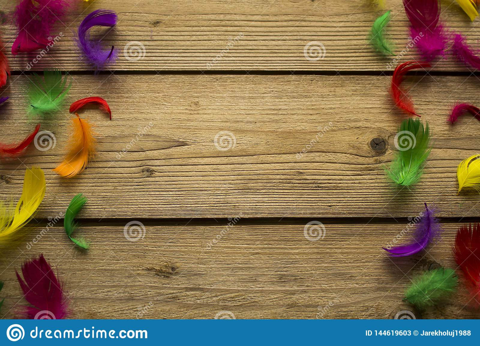 Colorful feathers on wooden table
