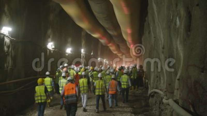 Construction Workers Walking Into A Large Tunnel Stock Footage