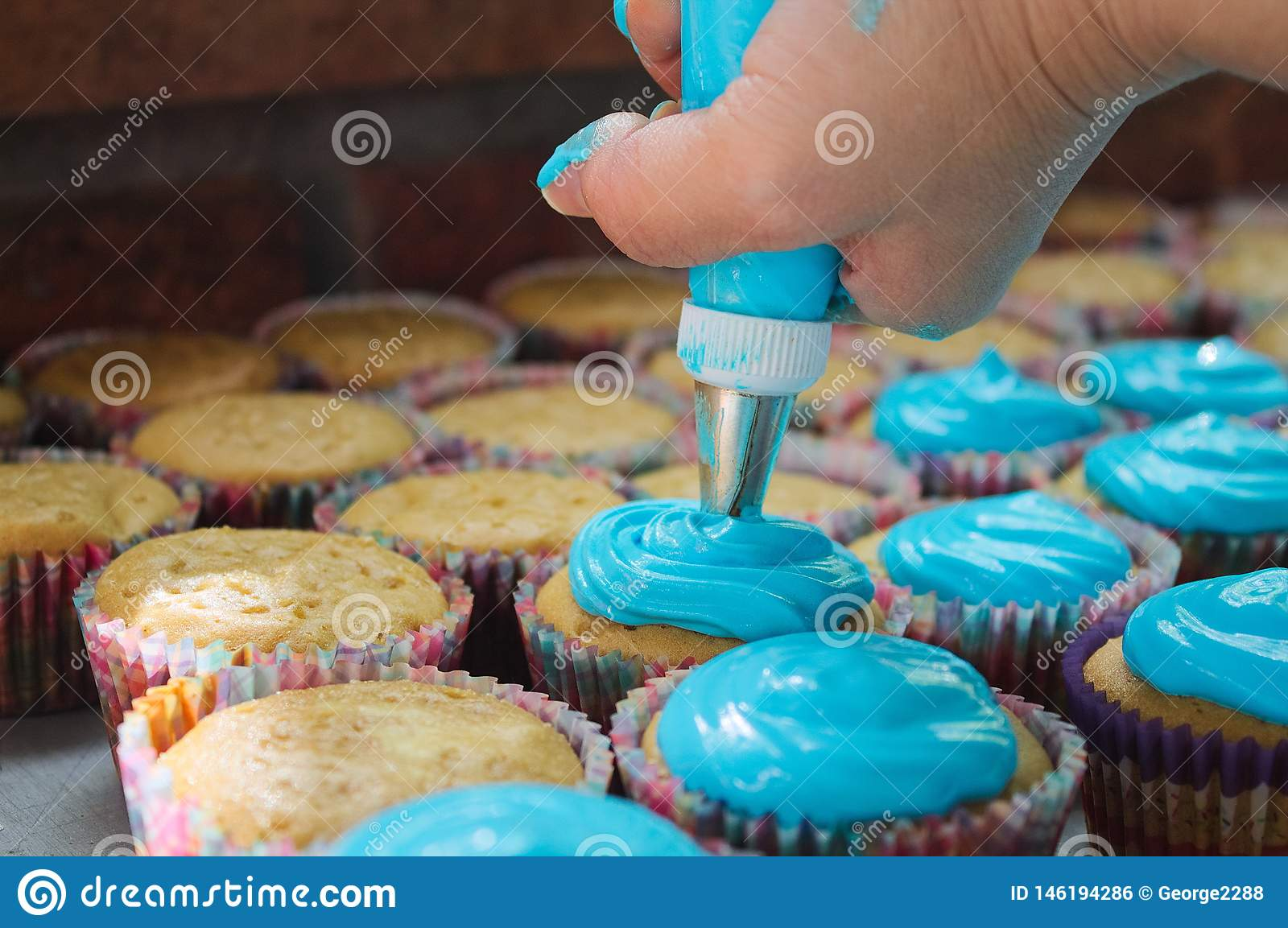 Many cutcakes being sprinkled with blue sweet cream