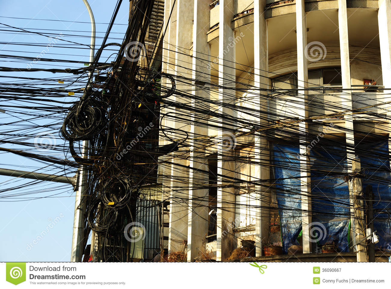 a mass of electric cables in a mess, in front of a house