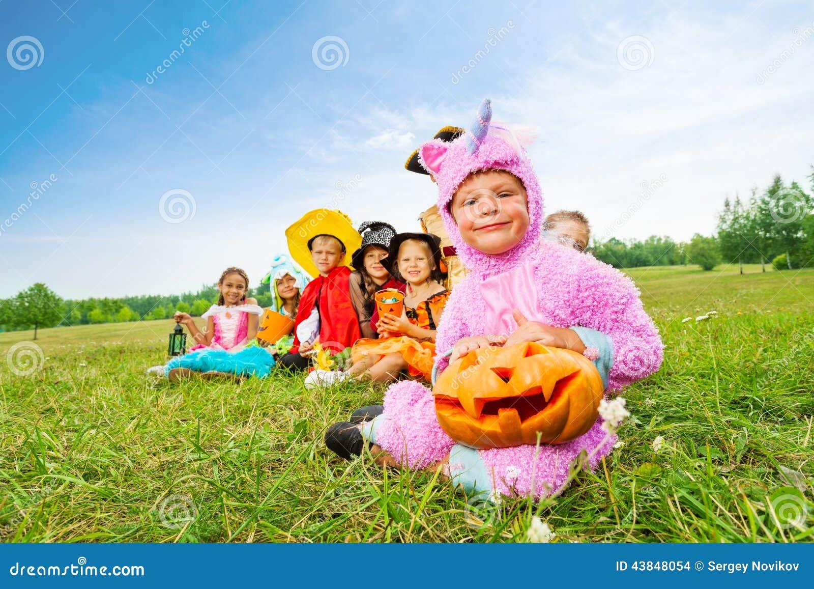Many Halloween kids wear costumes sit in long row
