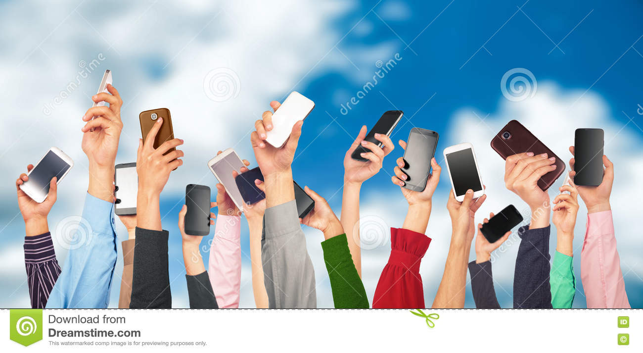 Many hands holding mobile phones against