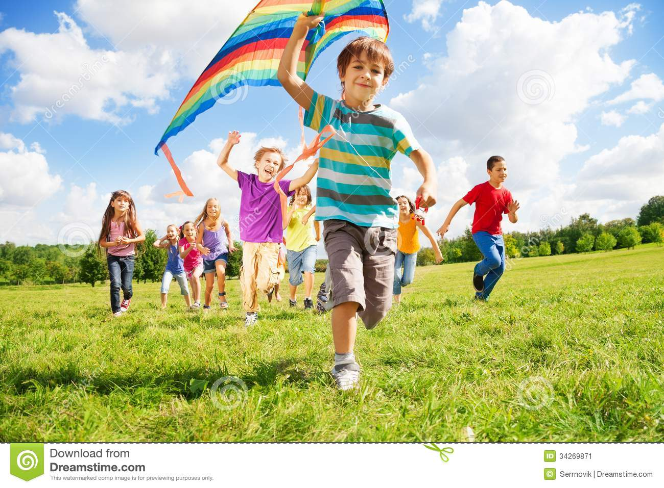 Many happy kids run together with kite on sunny summer day.
