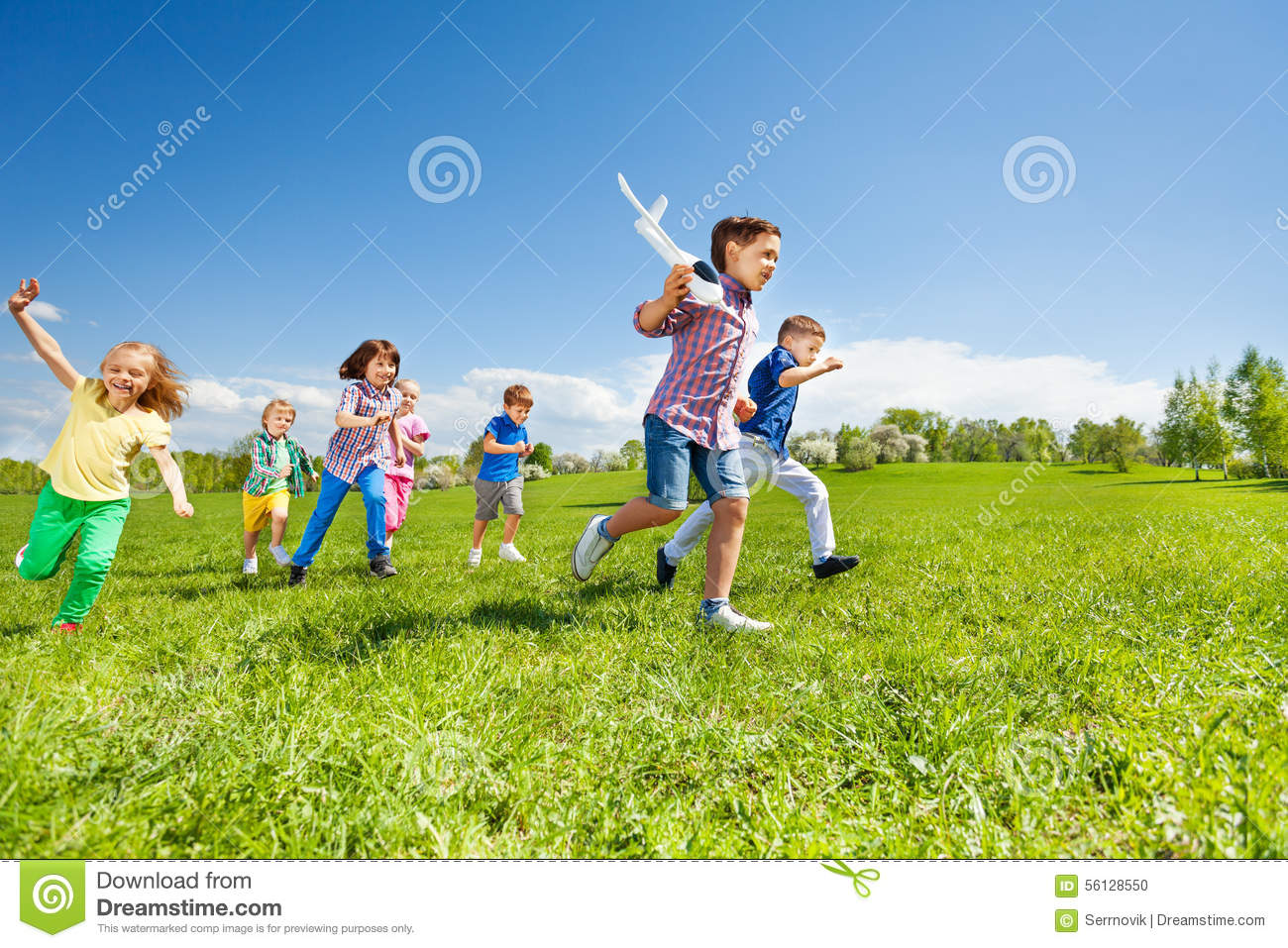 Many kids running and boy holding airplane toy