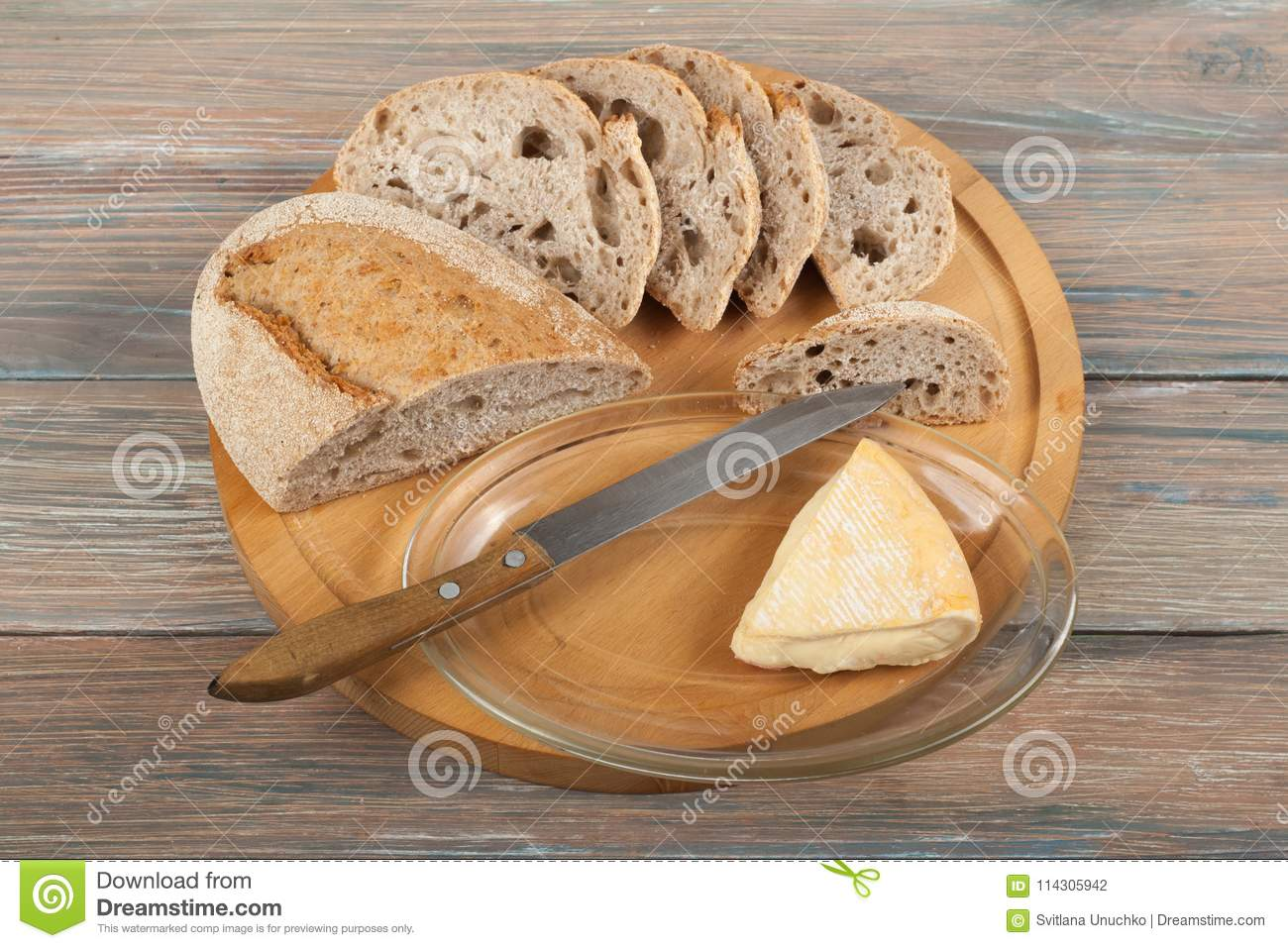 Many mixed breads and rolls of baked bread on wooden table background.