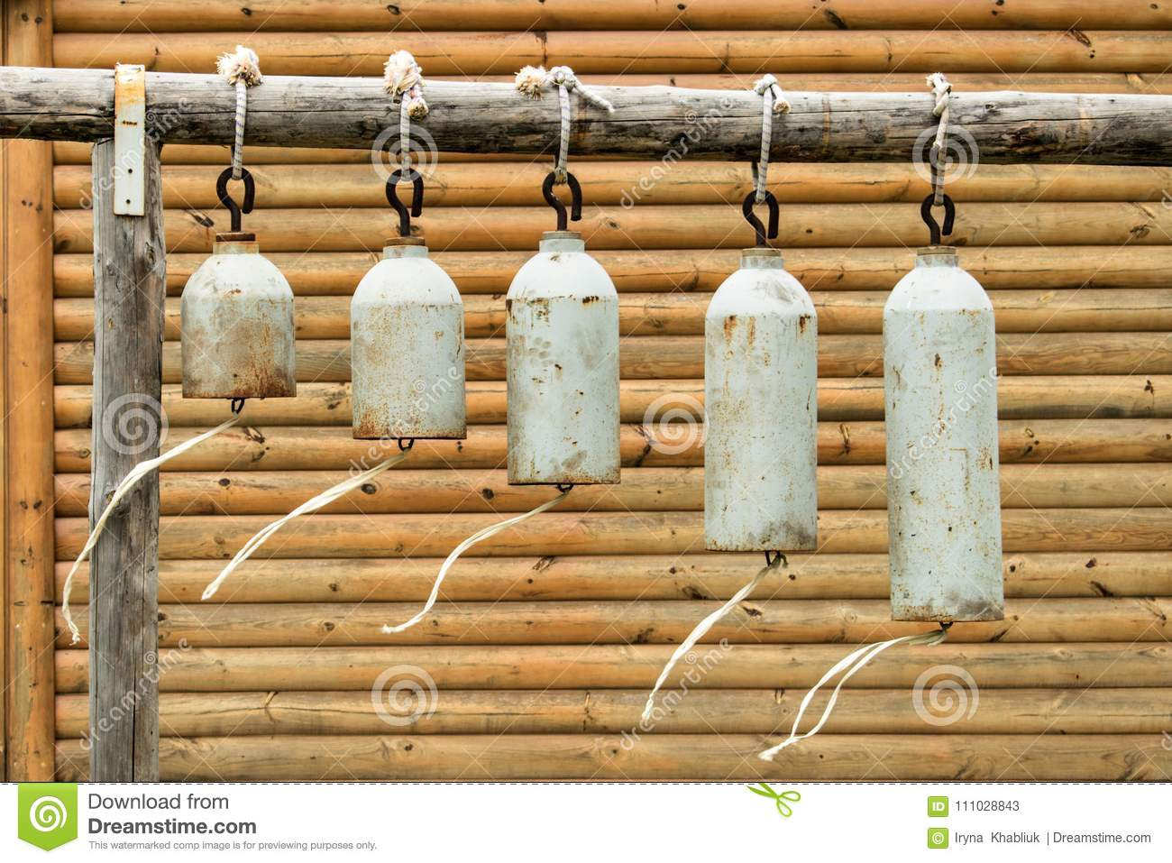 Many modern church bells hanging outside on the background of a wooden wall