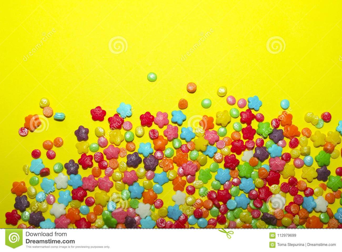 Many Multicolored Candy Sweets On Yellow Background.