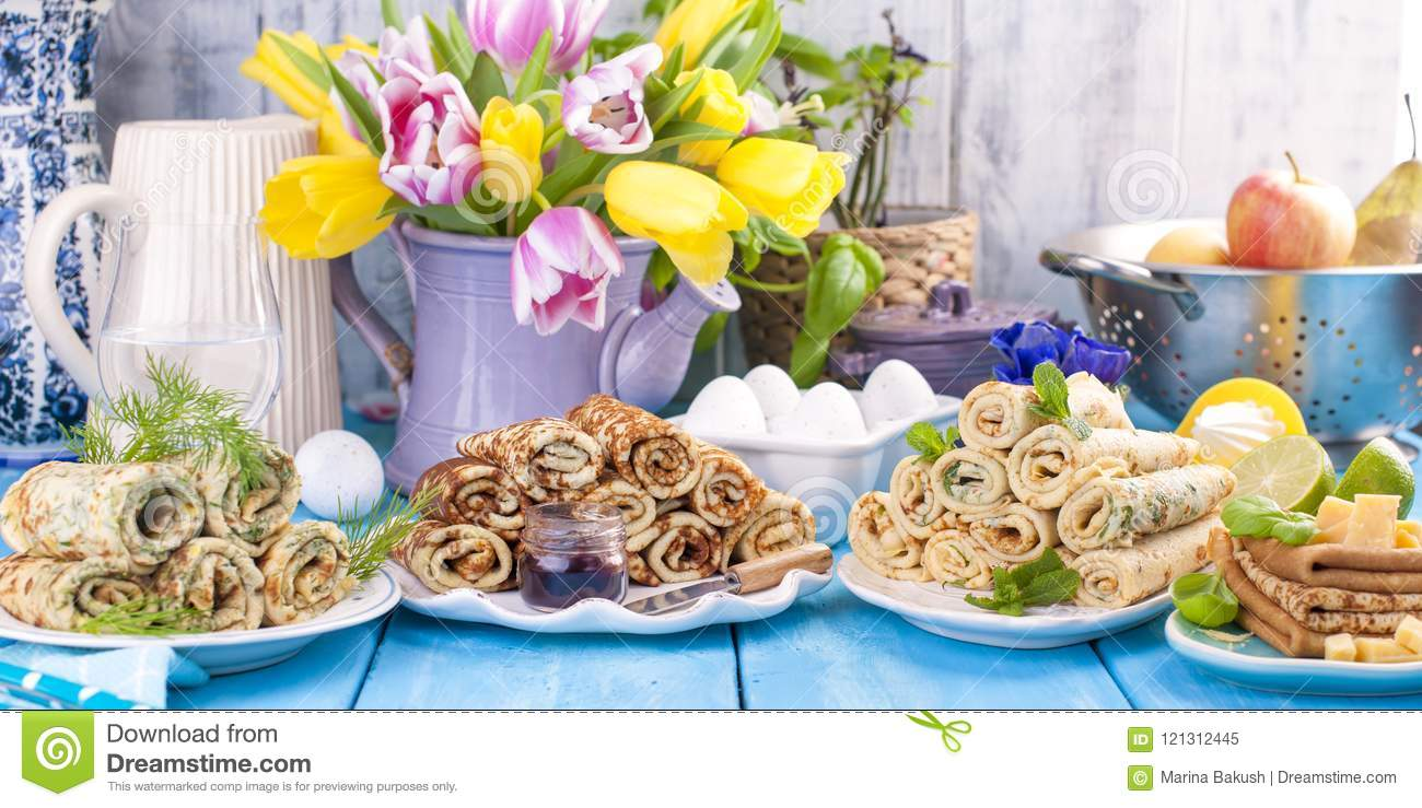 Many pancakes with different fillings and flavors. Delicious traditional food in the spring. Homemade baking. Flowers and
