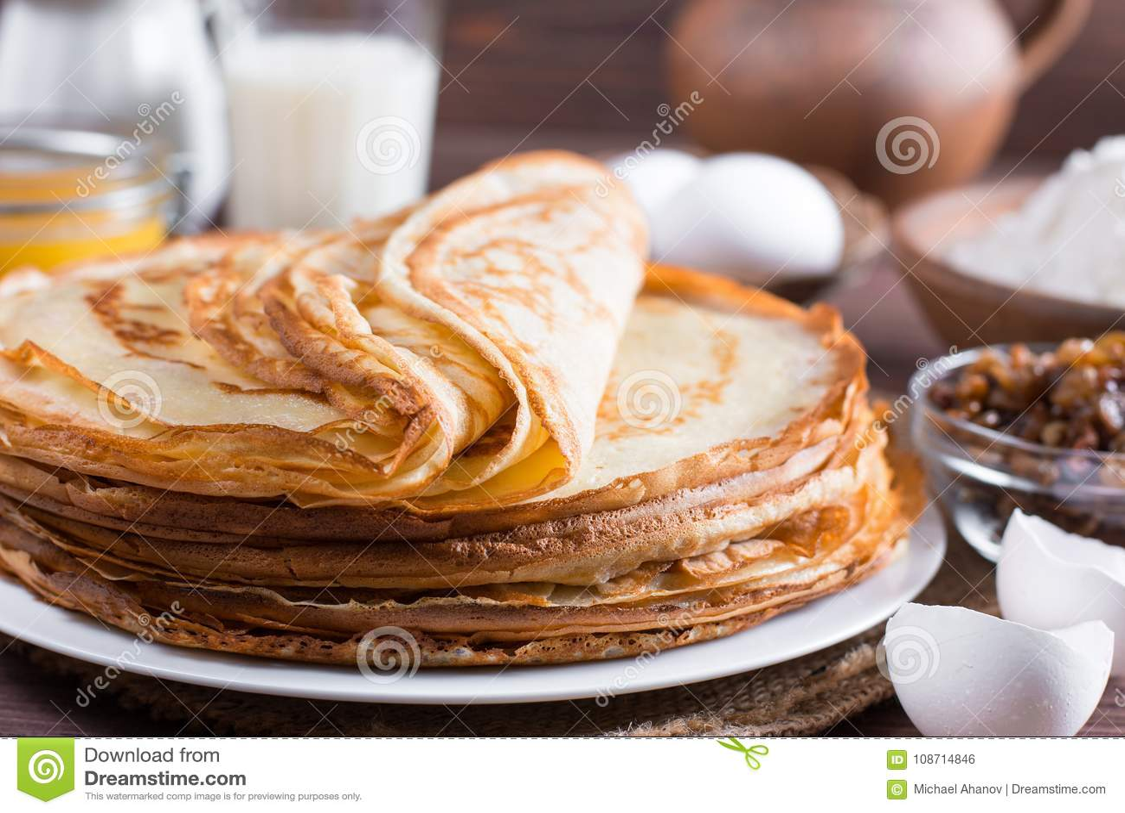 Many pancakes on a wooden background. Traditional Ukrainian or Russian pancakes. Shrovetide Maslenitsa.