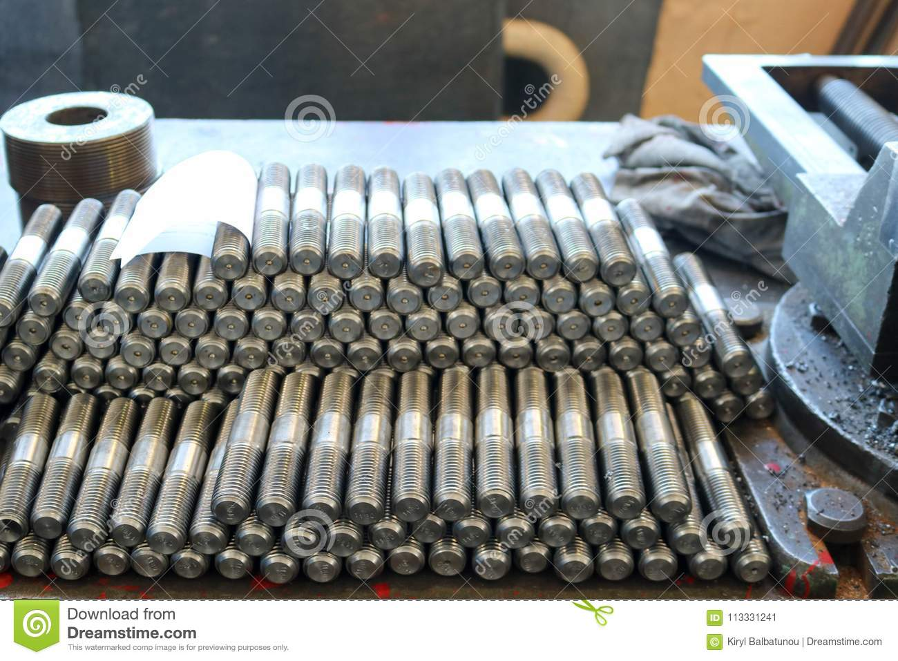 Many shiny metal studs with carving, nuts, iron rings, gaskets, metalwork tools and industrial vise