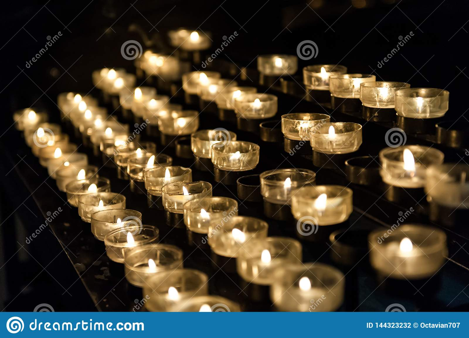 Many small candles in the church lightning in the dark