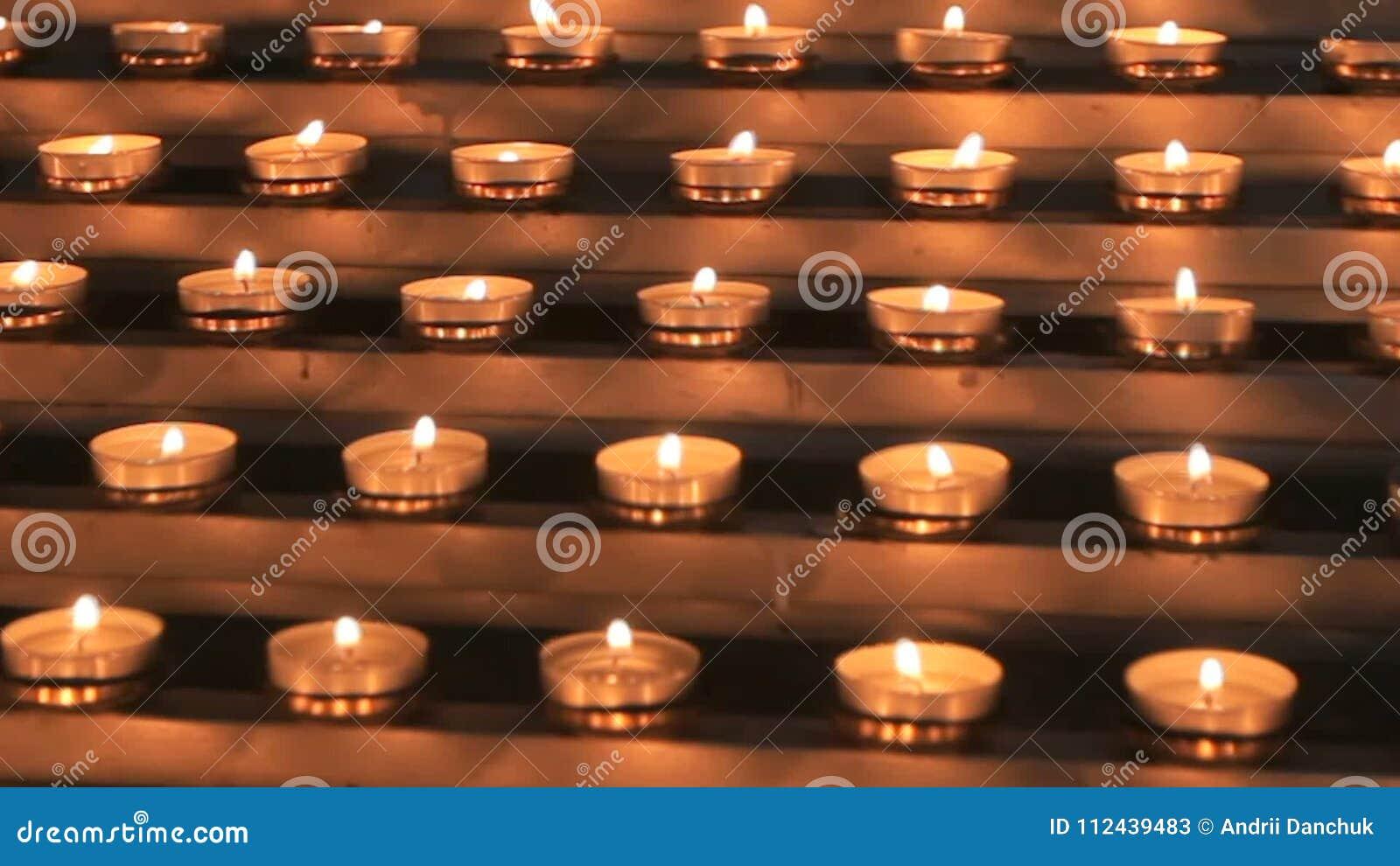 Many small church candles burn at the altar  Bright, celebration