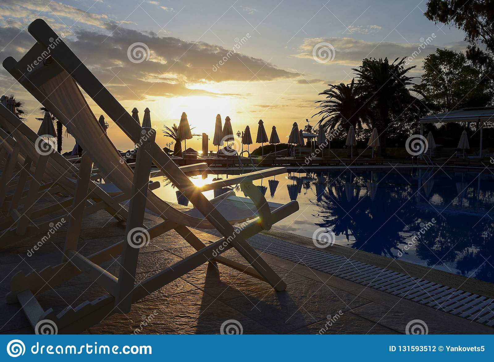 Many white chaise longues stand near the swimming pool against the backdrop of a dawn sky and beach umbrellas