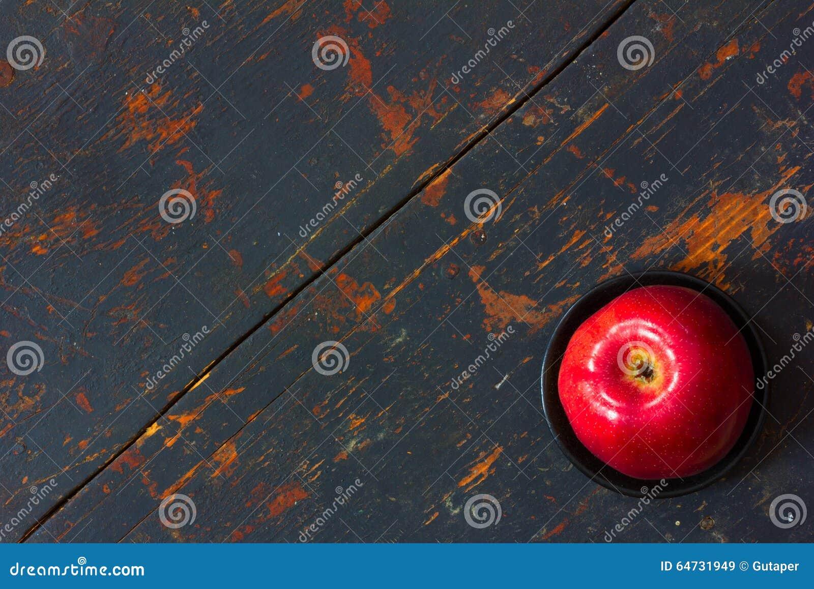 Manzana madura roja en un platillo negro en viejo fondo