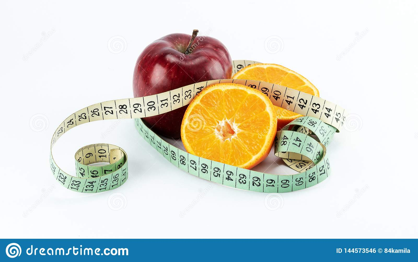 Manzana roja con dos mitades de las naranjas envueltas con la cinta métrica