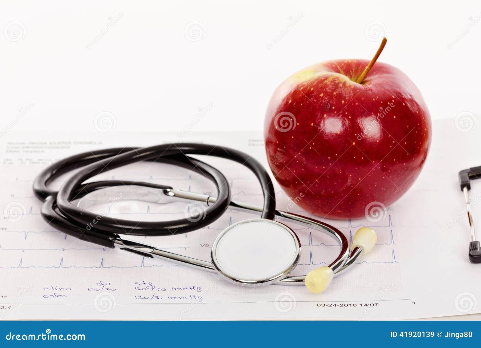 Manzana y estetoscopio rojos en una carta del electrocardiograma (ECG)