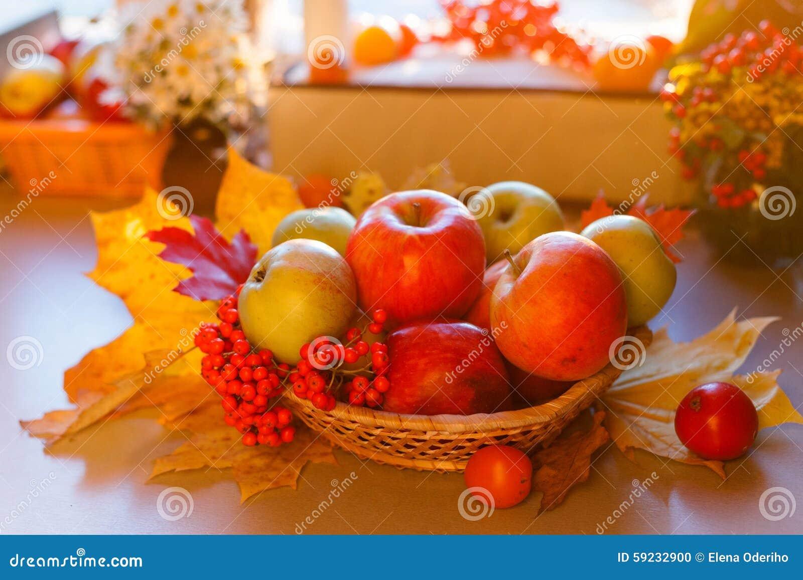 Manzanas maduras rojas con las hojas de otoño y el serbal