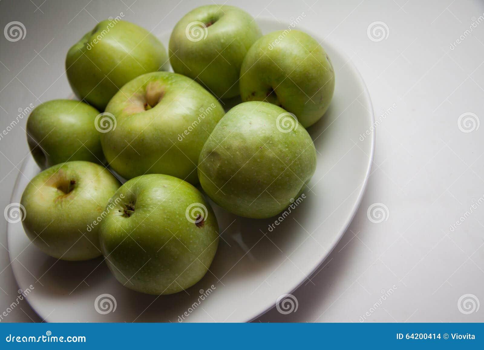 Manzanas verdes debajo del relámpago del contraste