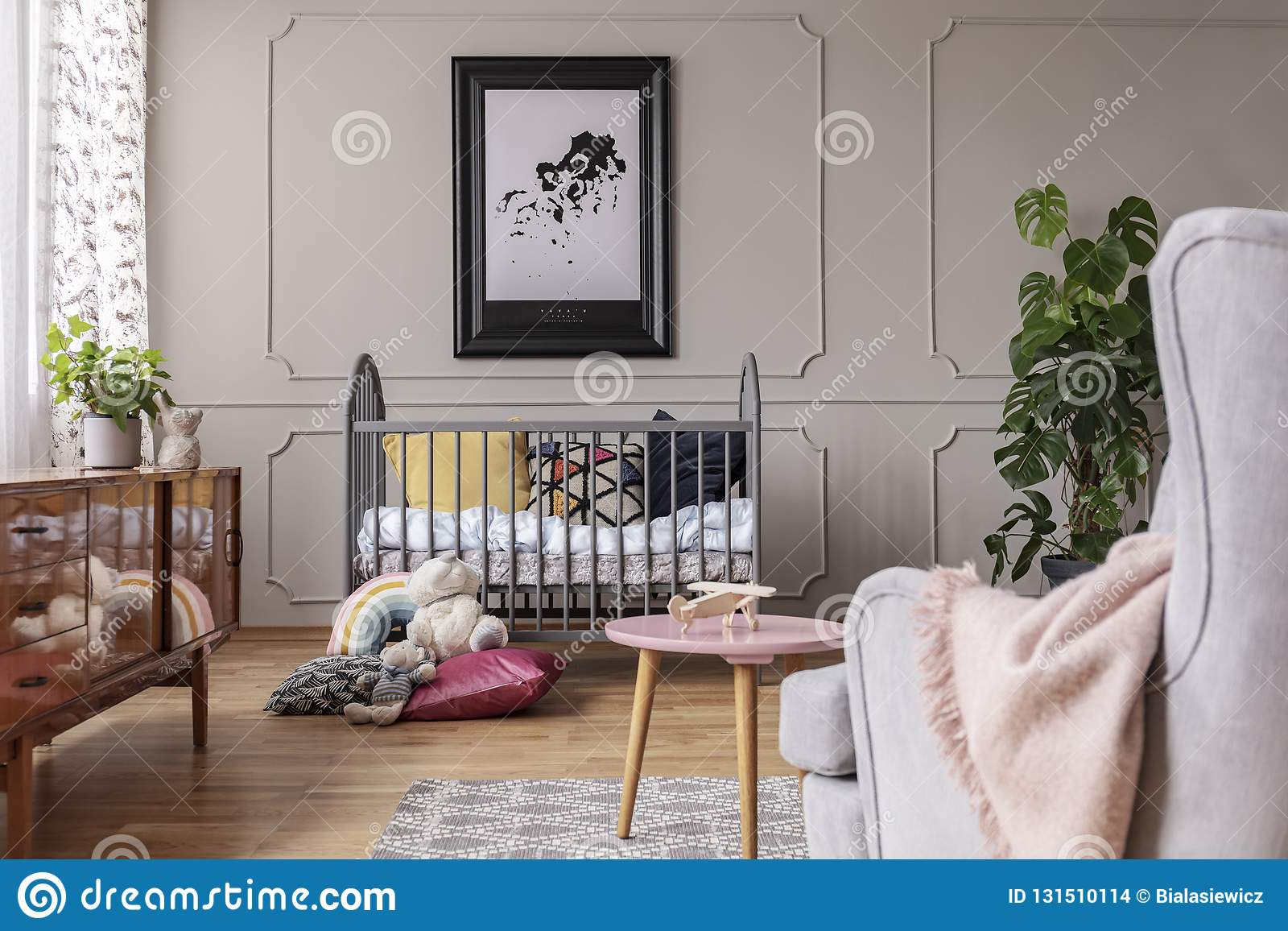 Map in black frame above grey crib