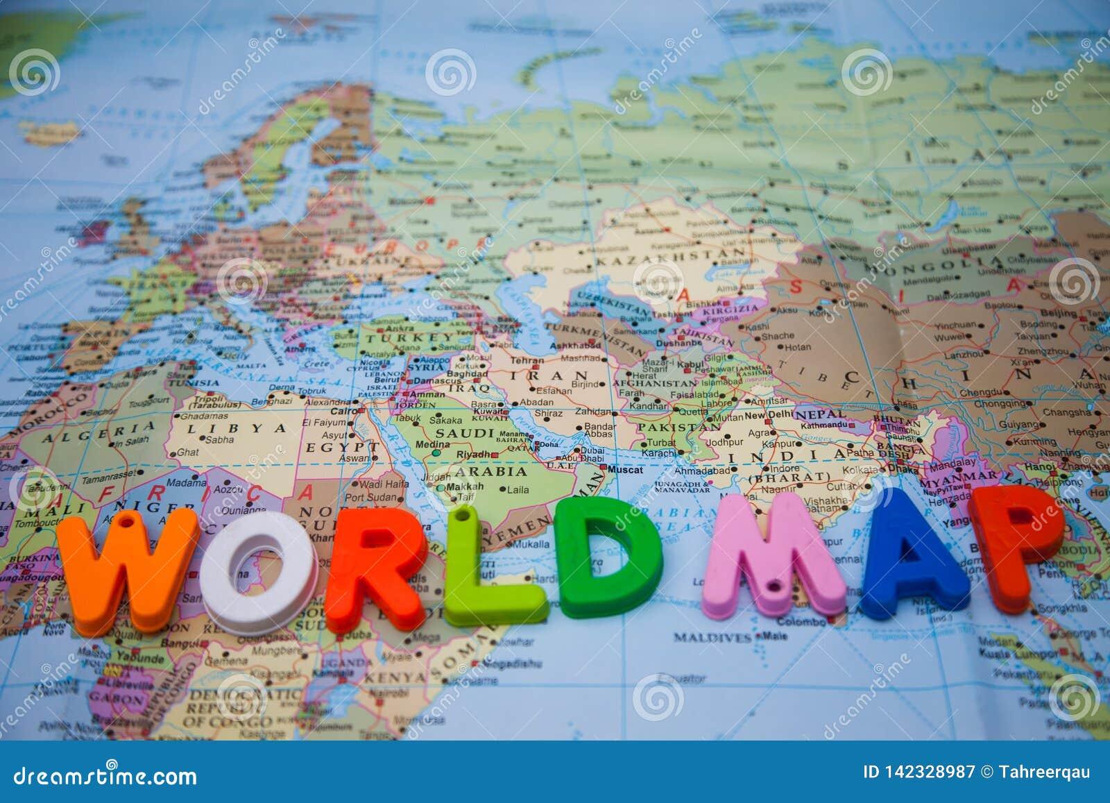 Mapa del mundo escrito con los bloques del juguete en un mapa del mundo