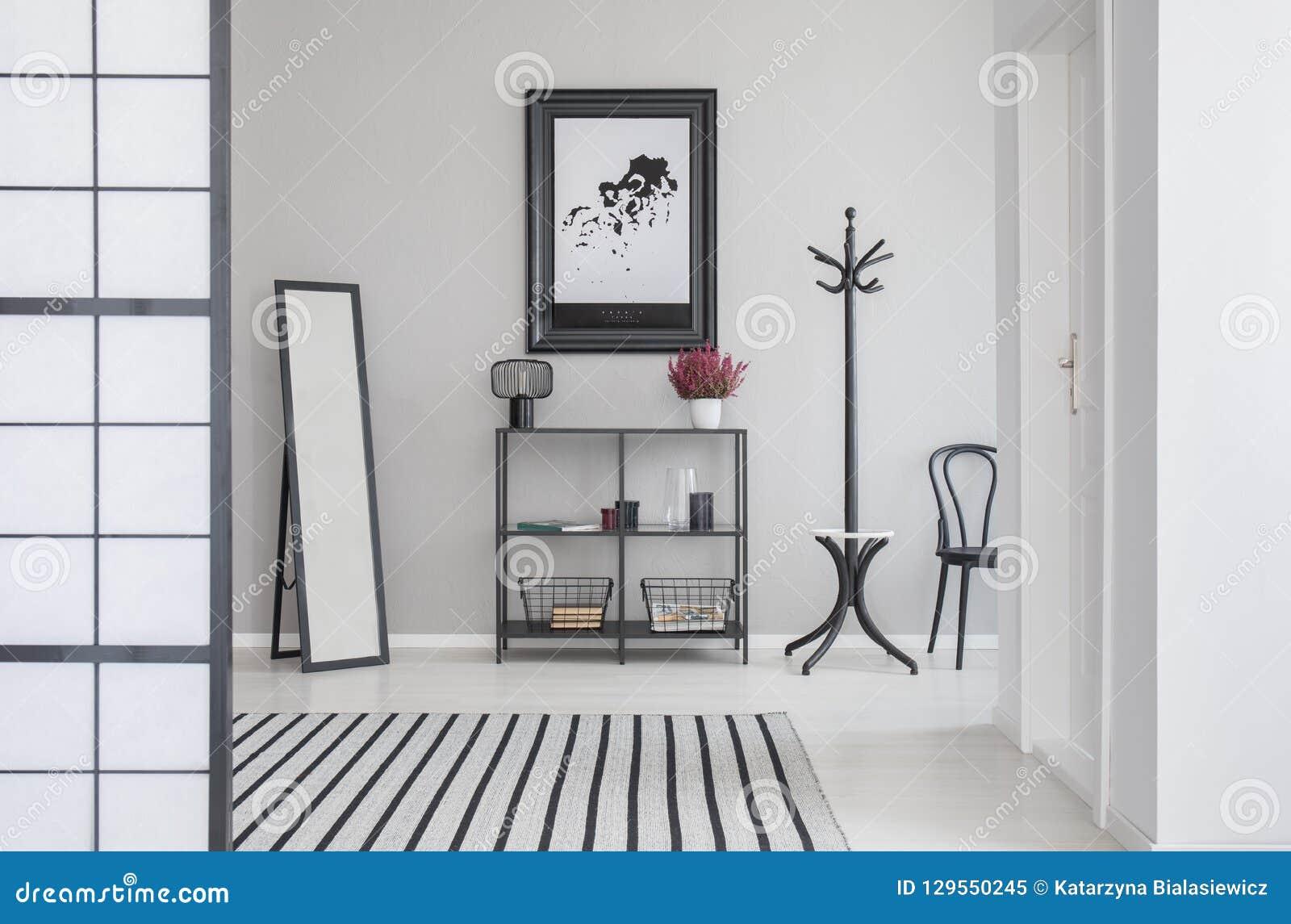 Mapa w czerni ramie na popielatej ścianie korytarz z lustrem, półką, wieszakiem i włosy,