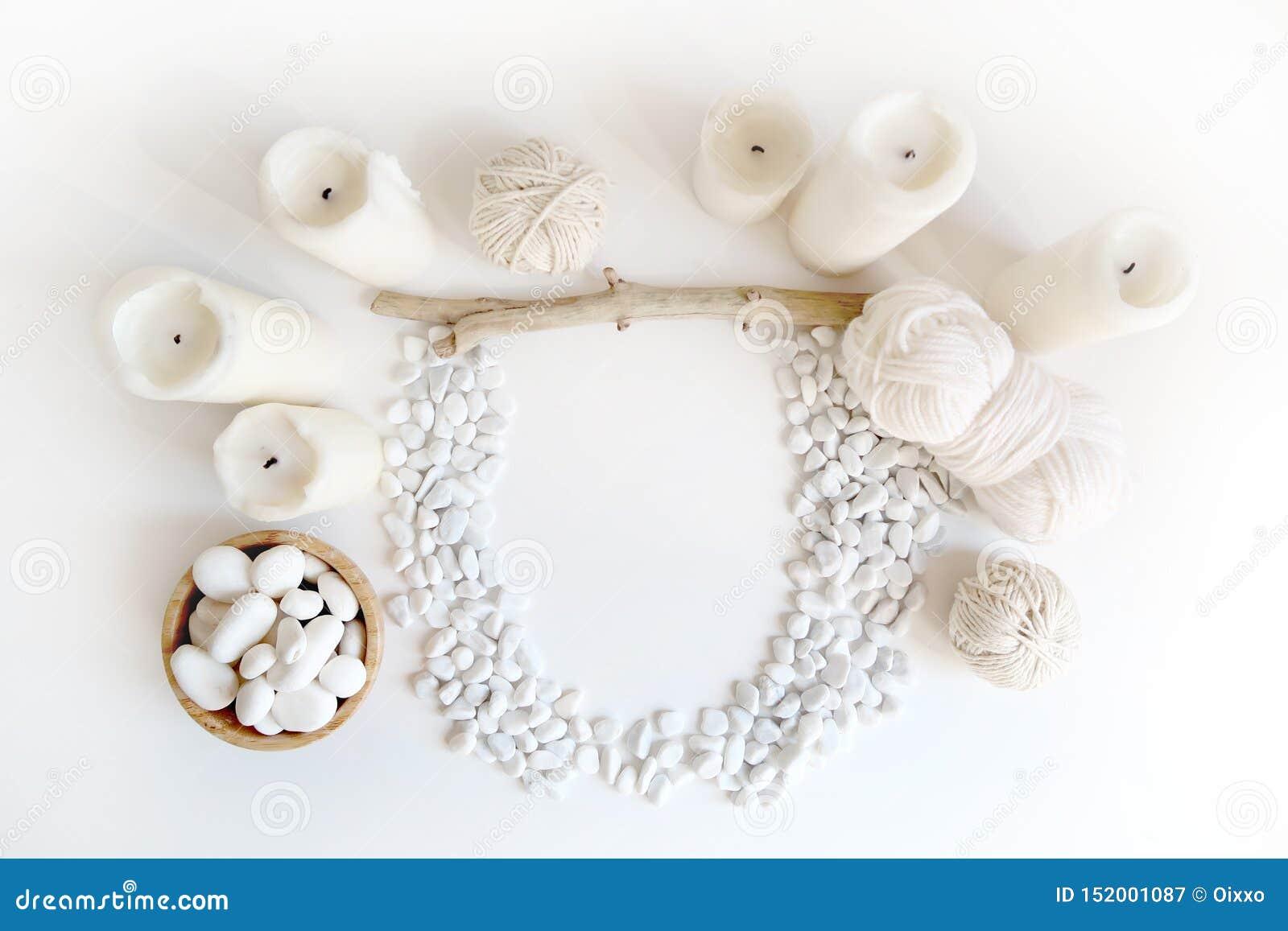 Maqueta blanca de Boho con las velas, el hilo de algodón y el guijarro del mar blanco en el escritorio Endecha del plano de la vi