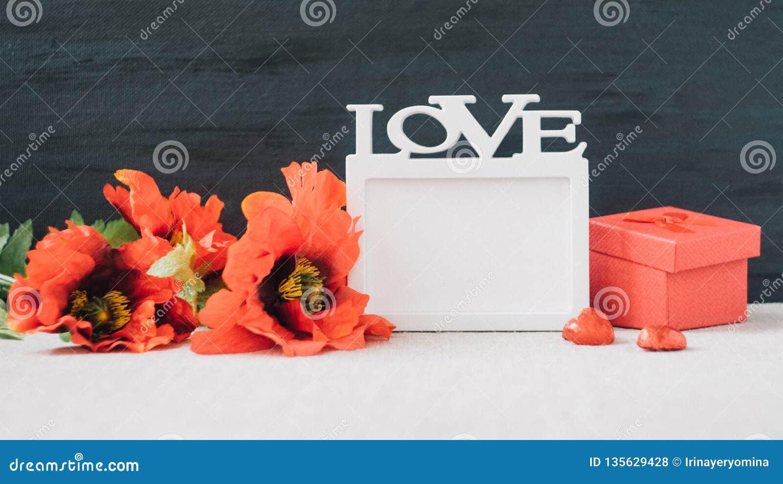 Maqueta de día de San Valentín con el marco blanco con la palabra AMOR, flores rojas de las amapolas y caja de regalo en tela y f