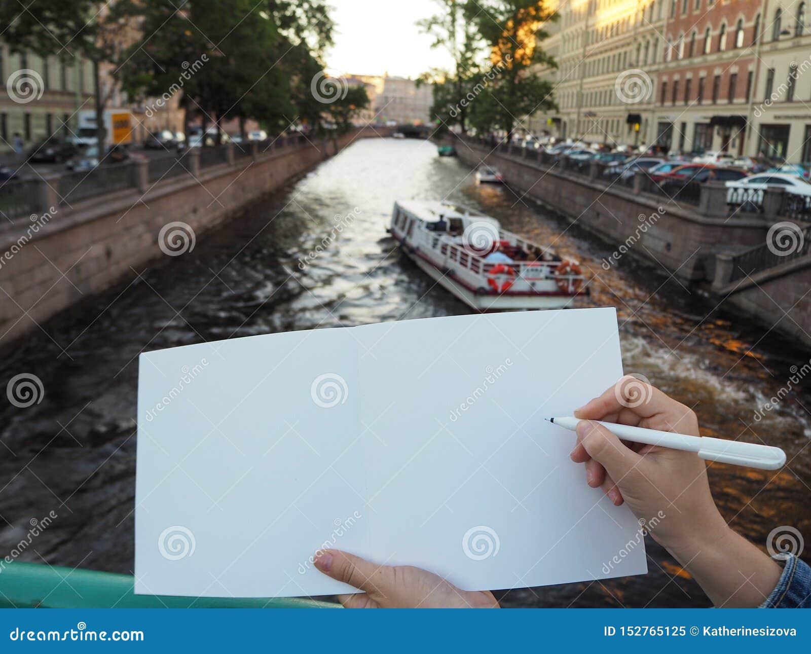 Maqueta de la mano de la persona que sostiene el cuaderno blanco en blanco que se prepara para anotar el suyo o el suyo ideas
