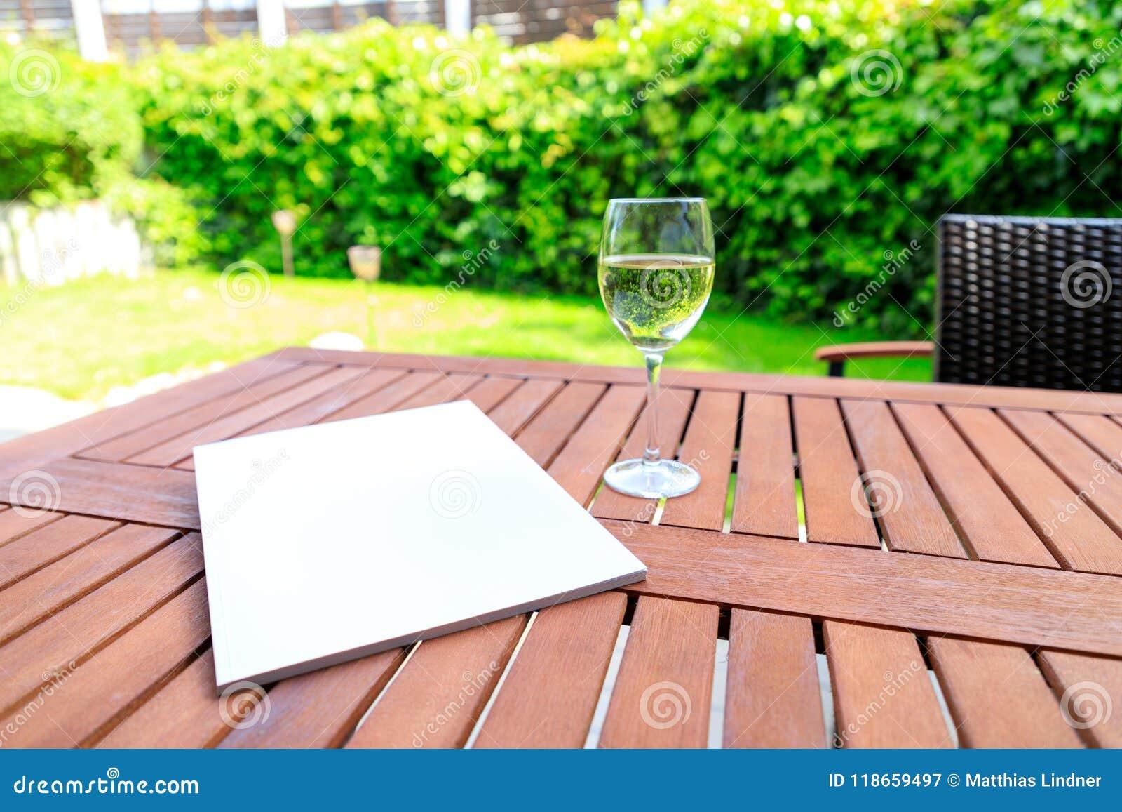 Maquette d une couverture de magazine sur une table en bois dans le jardin au su