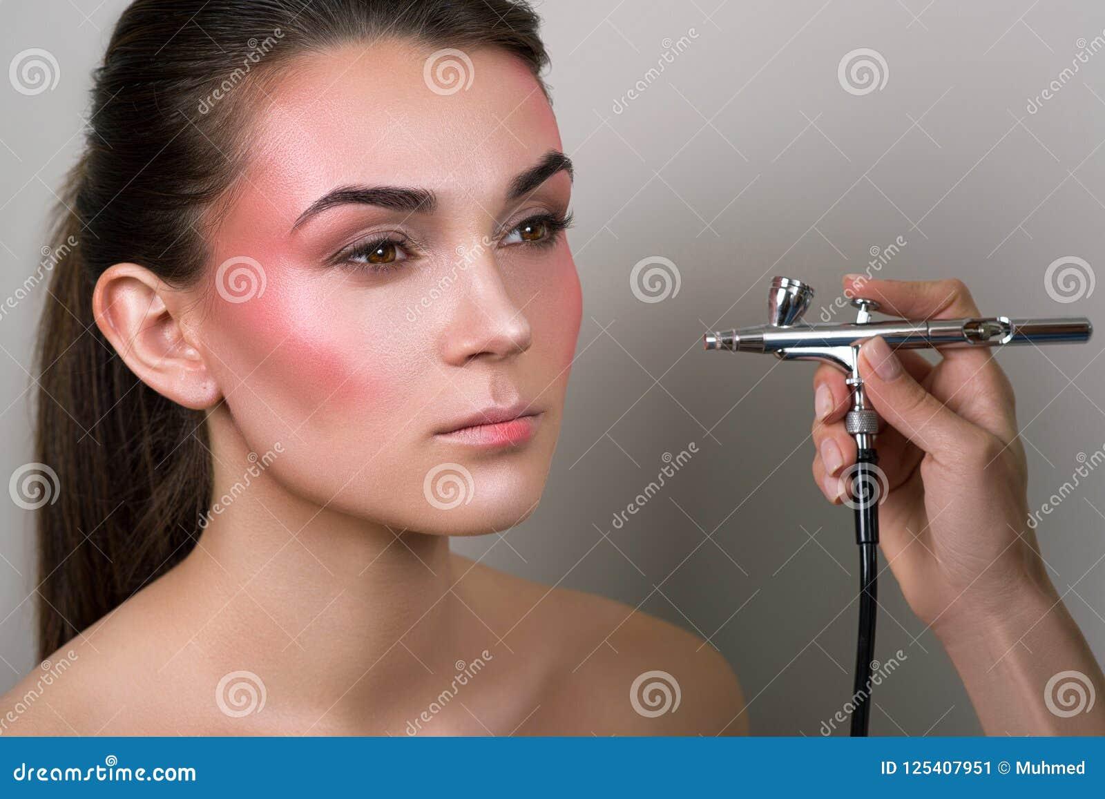 Maquilleur faisant le maquillage professionnel de la jeune femme Détail de maquillage peau parfaite de fille de beauté Beauté, co