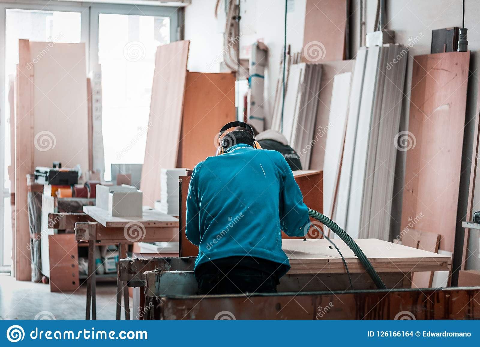 Maquinaria de madera del corte del CNC, operador con el funcionamiento azul de la camisa