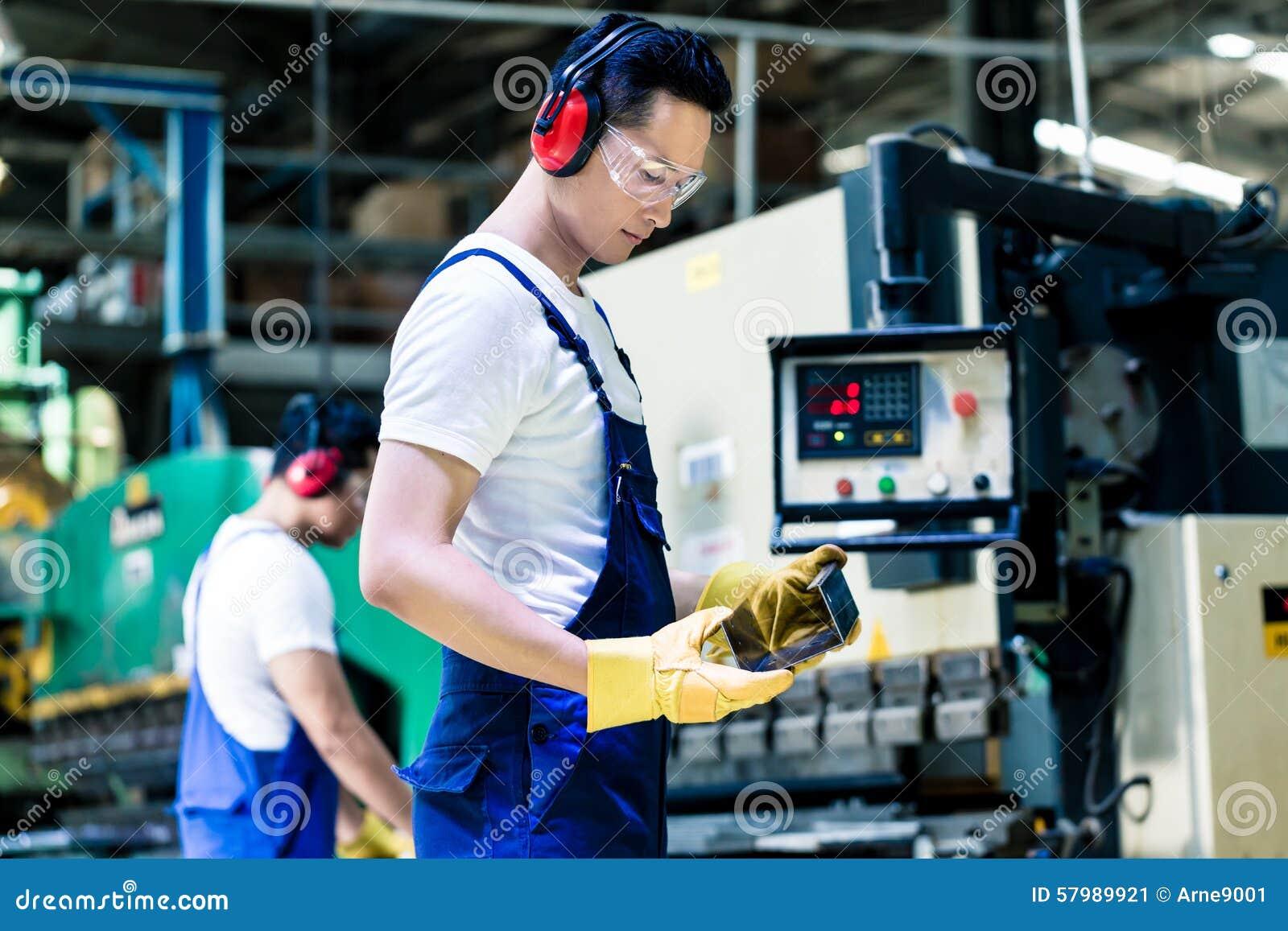 Maquinista asiático en la instalación de producción