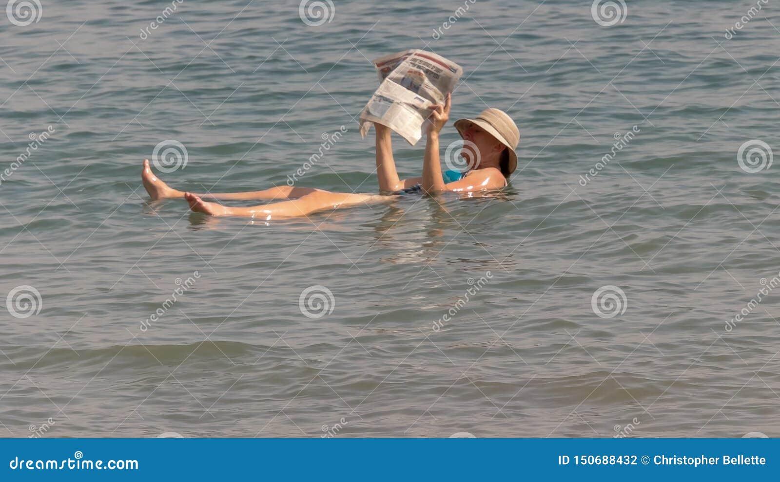 MAR MUERTO, ISRAEL - SEPTIEMBRE, 22, 2016: mujer que lee un periódico mientras que flota en el mar muerto de Israel
