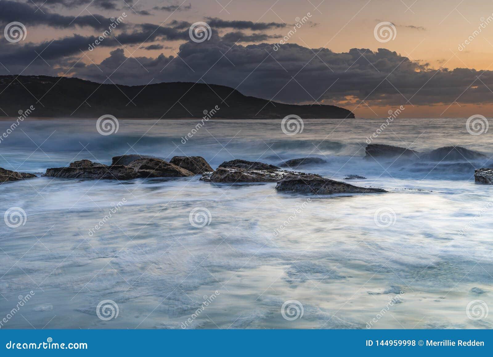 Mar, promontório, nuvens e nascer do sol