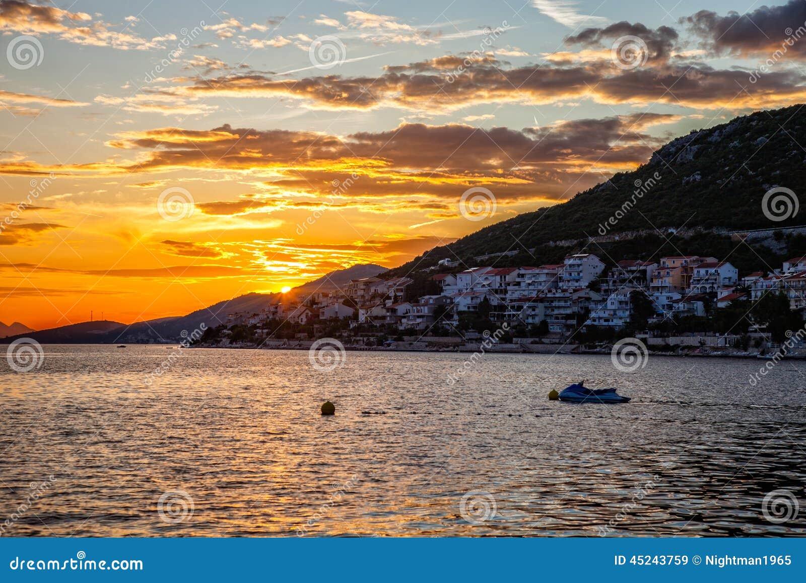 Mar y montañas en la puesta del sol - silueta