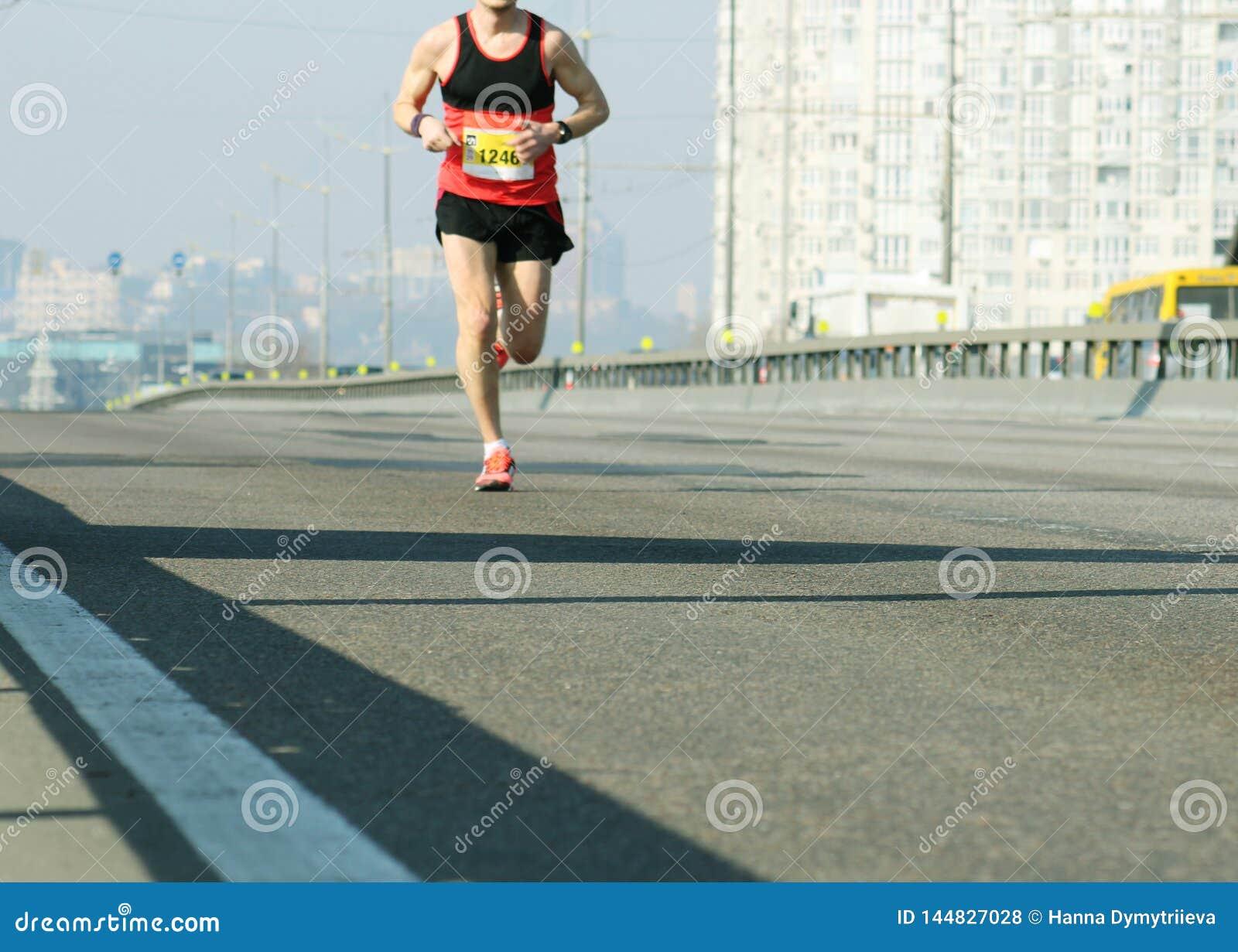 Marathon die in het ochtendlicht lopen Jonge mens die op stadsbrug lopen Het lopen op stadsweg De voeten van de atletenagent Blur