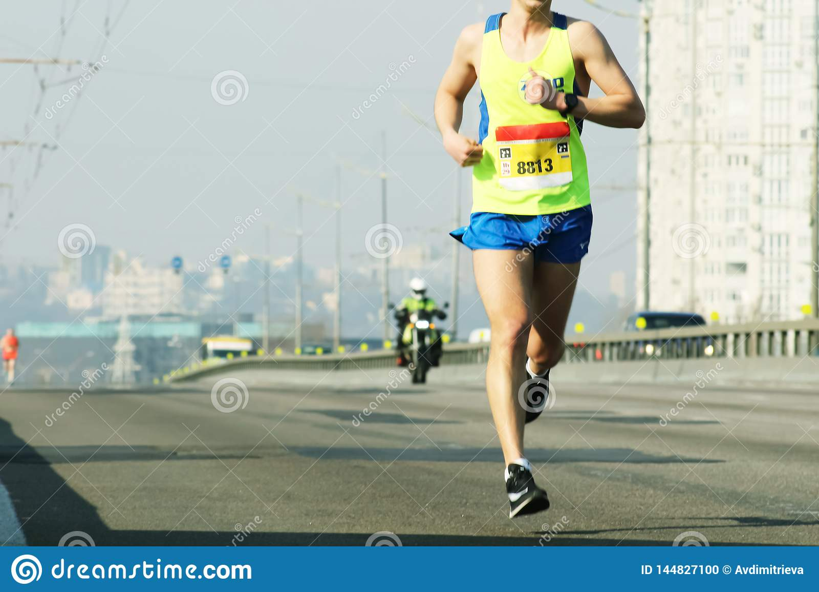 Maratonspring i morgonljuset K?ra p? stadsv?gen K?ra f?r idrottsman nenl?parefot L?parespring f?r ung kvinna p? stad