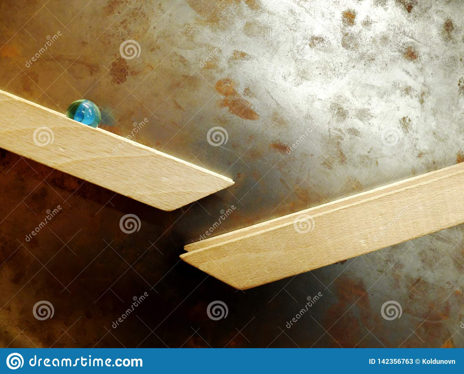 Marble ball rolling down along the wooden rail magnetically attached to the metal rusty wall. The concept of downward movement and