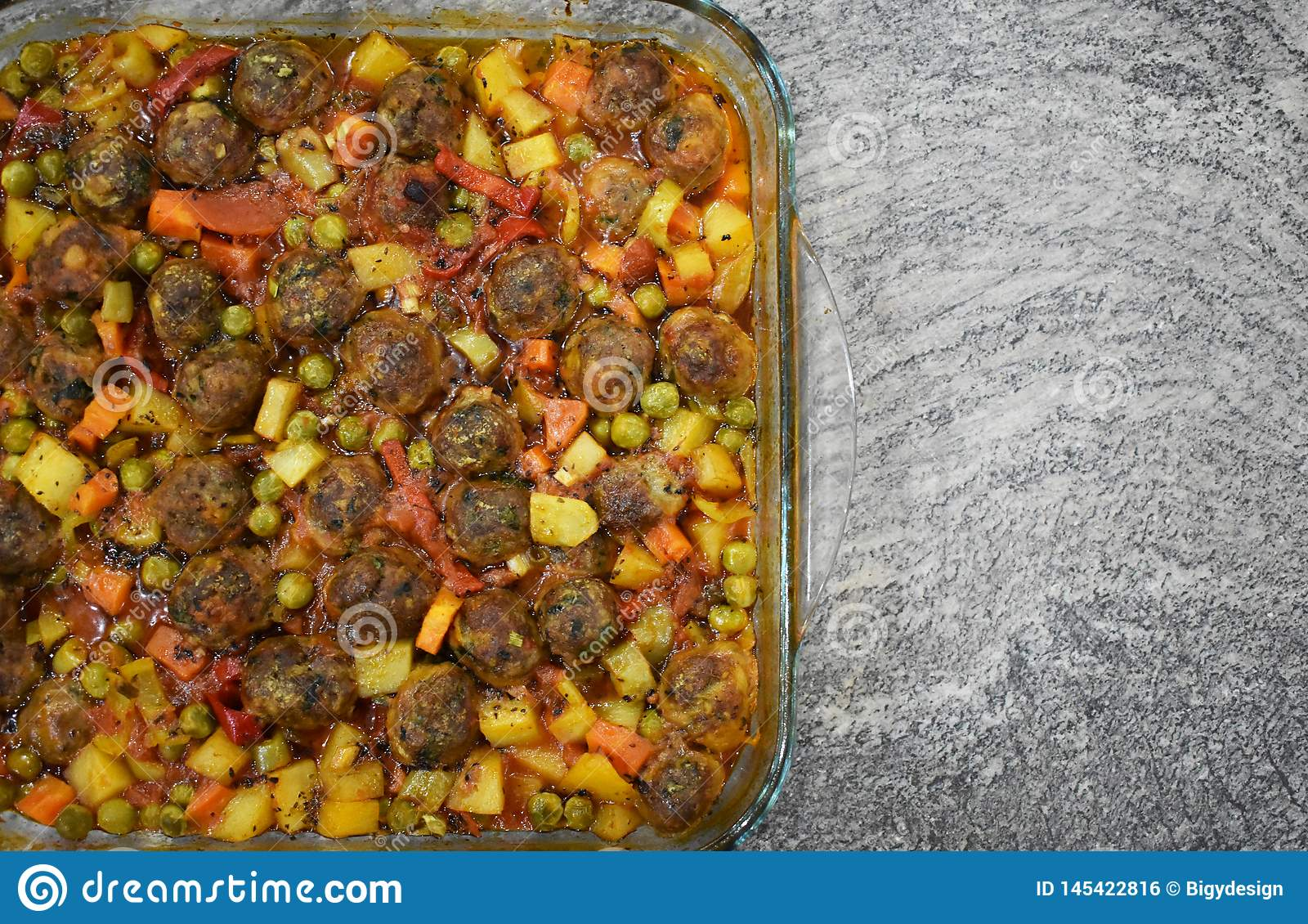 On marble floor, meatballs with vegetables, in glass baking dish