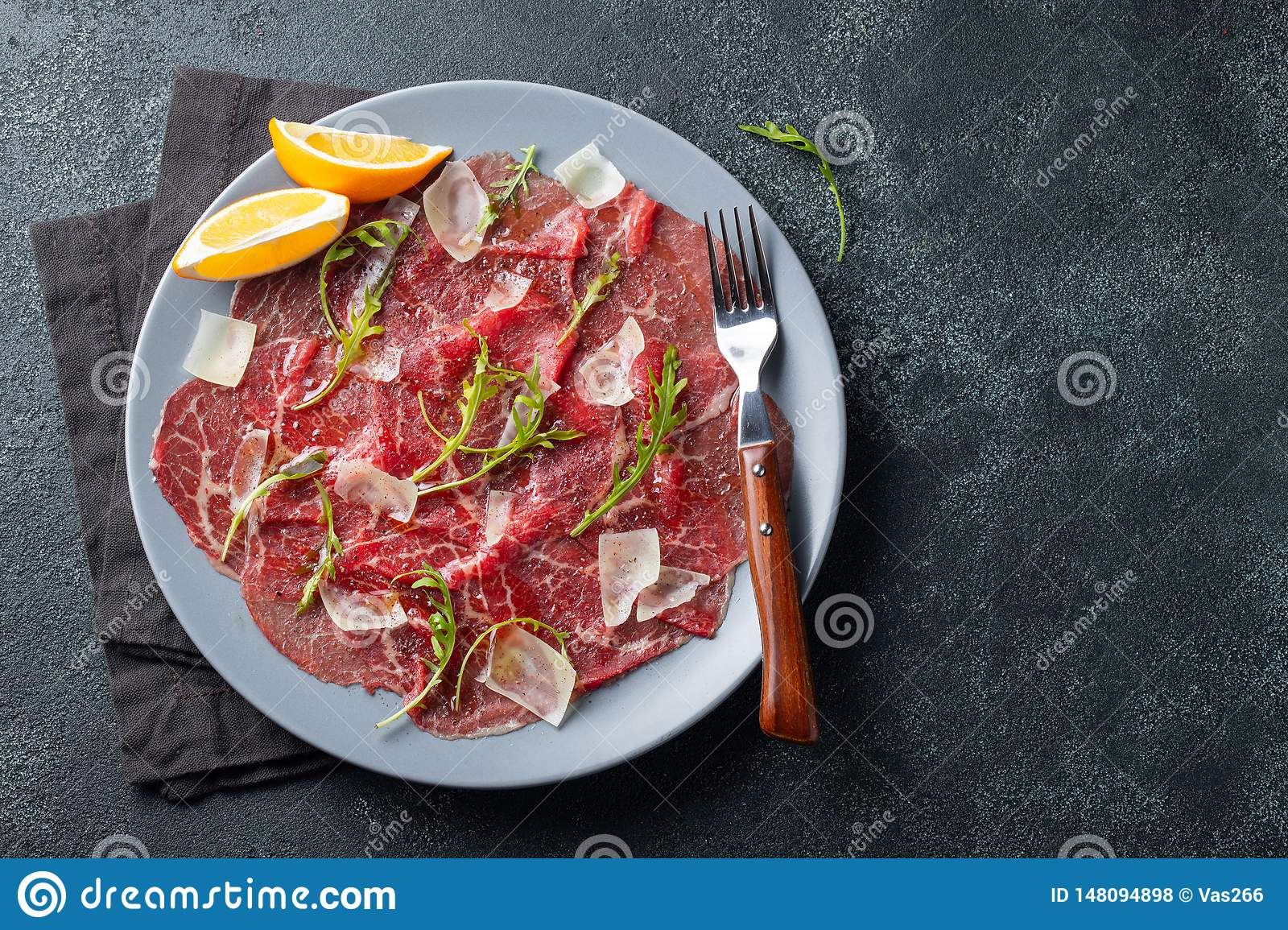 Marbled beef carpaccio with arugula, lemon and parmesan cheese on dark concrete table. Top view, flat lay with copy