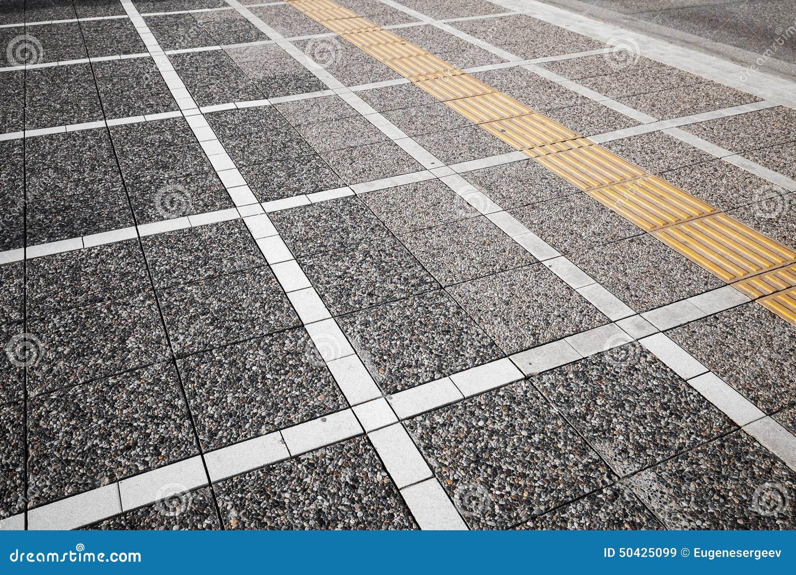 A marcação de estrada branca e amarela alinha na pedra cinzenta