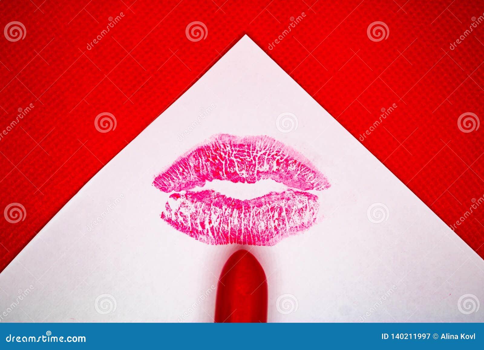 Marca del beso y la barra de labios roja en el Libro Blanco con el fondo rojo - imagen