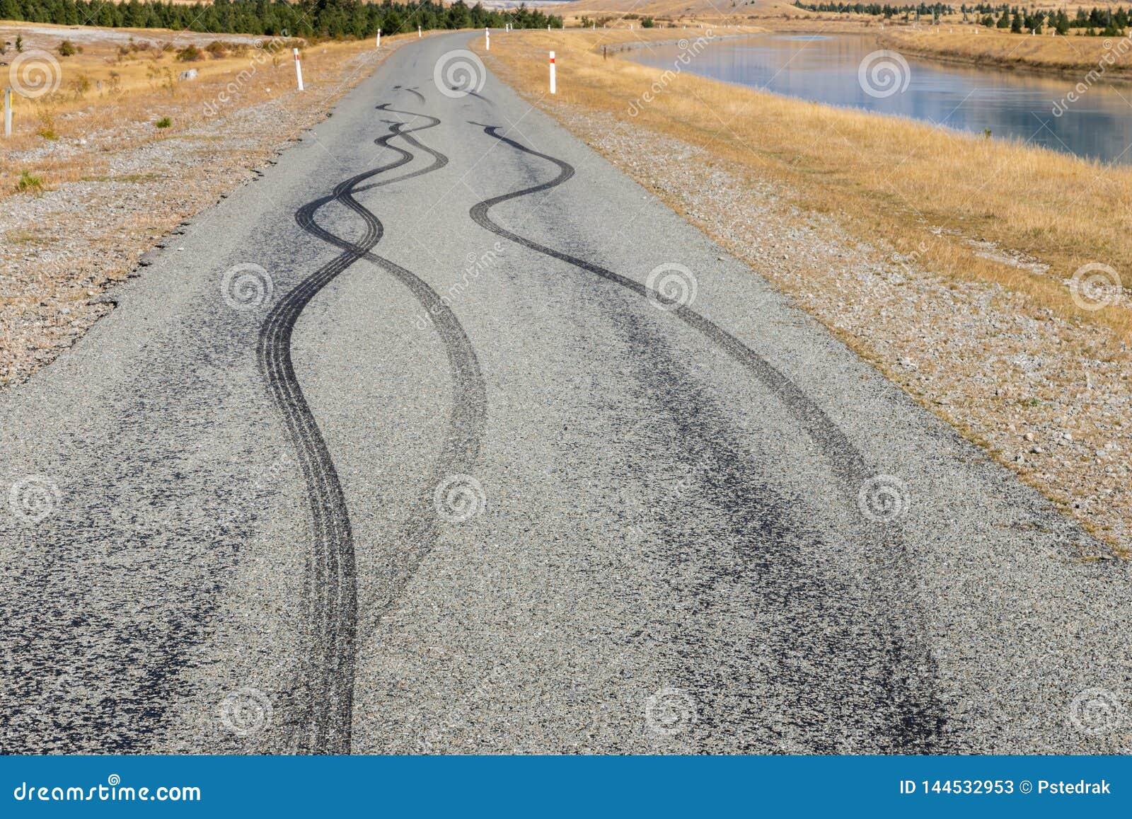Marcas de patim de borracha pretas do pneumático na estrada do alcatrão