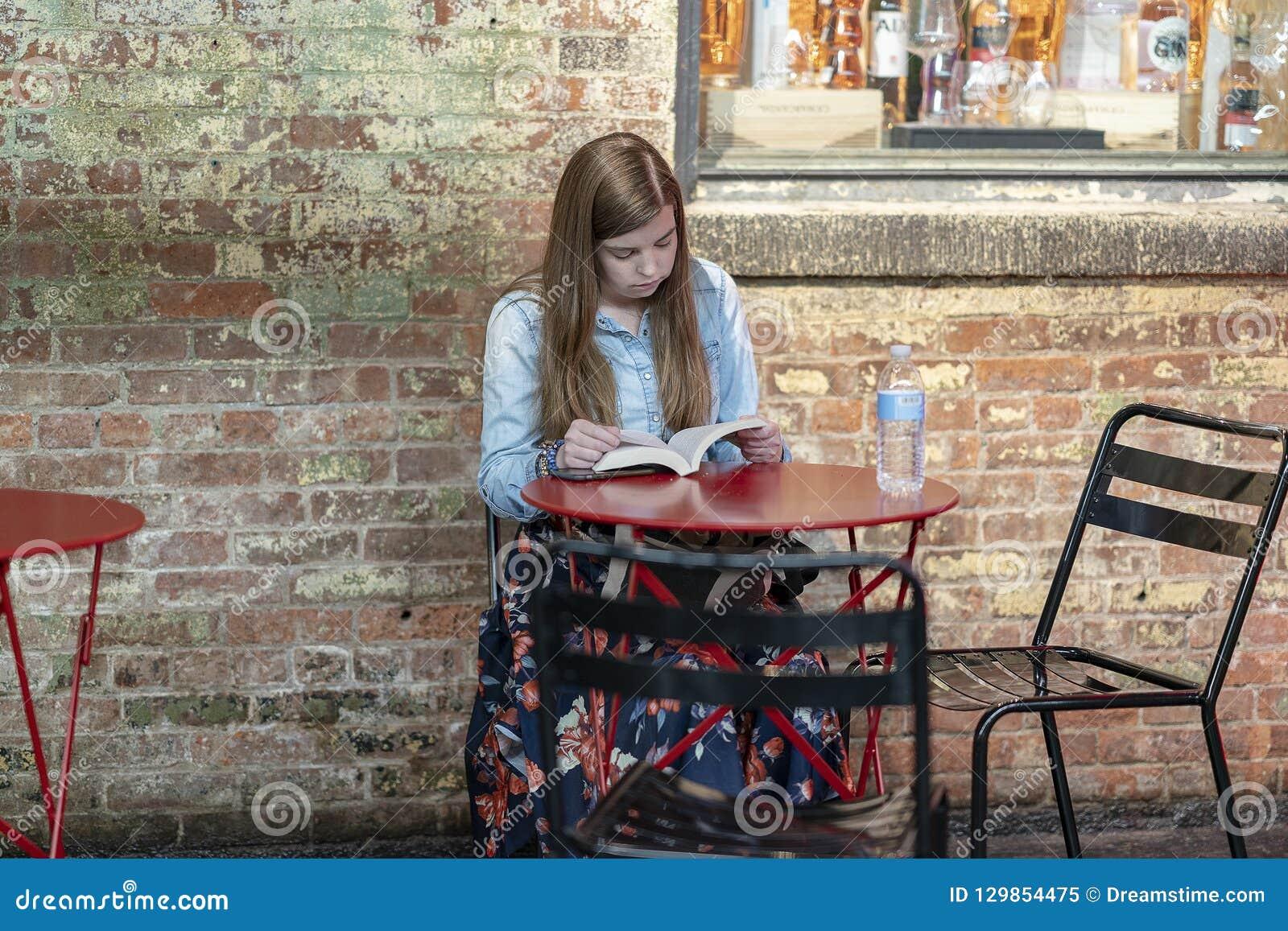 MARCHÉ de CHELSEA, NEW YORK CITY, Etats-Unis - 21 juillet 2018 : Livre de lecture de jeune fille en café